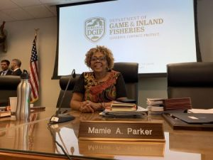 Dr. Mamie Parker sits at a large table with a nameplate. She is seated in an executive chair in front of a screen that says Dept of Game & Inland Fisheries